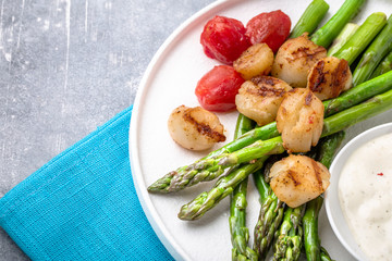 Grilled scallops with asparagus and sauce on white plate, closeup