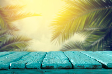 Fototapeta Summer background of wooden table and beach background with palms
