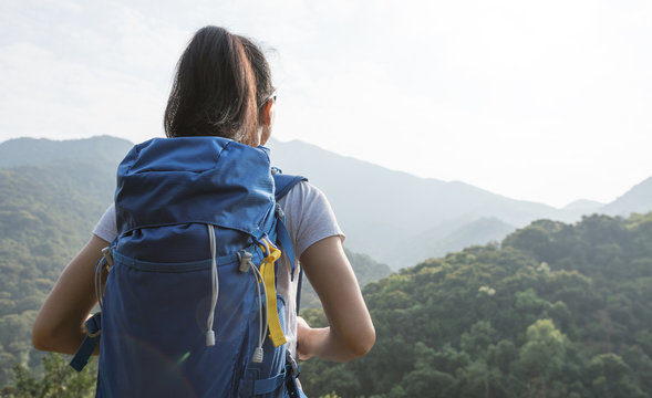 woman backpacker enjoying the view on morning mountain valley