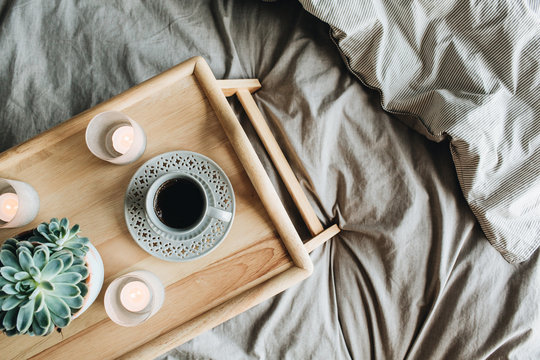 Morning breakfast in bed with coffee. Flat lay, top view lifestyle still life composition with wooden tray and grey linen.
