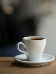 Coffee in white mug on a wooden floor, Close-up shoot vertical image.