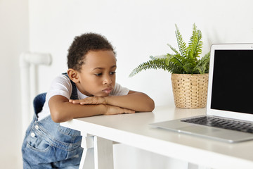 People, childhood, technology and modern electronic gadgets. Upset sad African American schoolboy feeling bored, pouting lips, forbidden to use internet, looking at laptop with disappointment