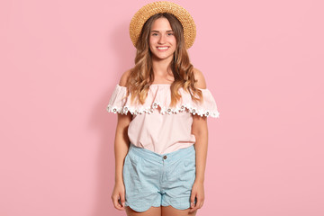 Happy girl posing in straw hat, rose summer blouse and blue short. Beautiful woman has charming smile, being in good mood, expresses happyness, looking directly at camera, standing isolated on pink. Wall mural