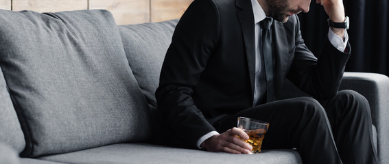 panoramic shot of depressed man sitting on sofa with glass of whiskey Wall mural