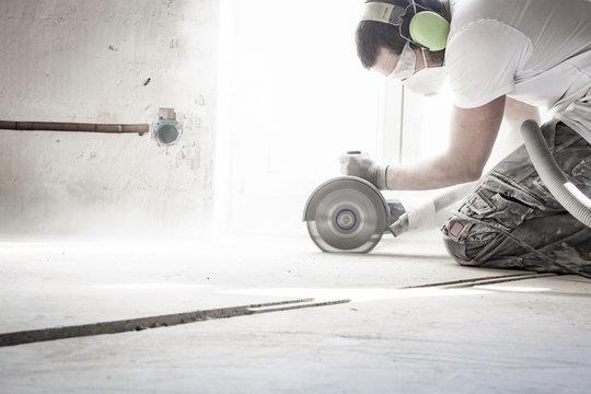 Bauarbeiter schneidet in Beton mit großer Flex auf der Baustelle