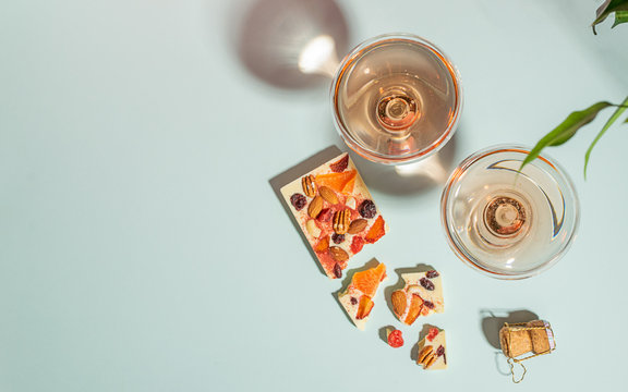 Drink champagne or wine in two elegant glasses and a bar of white chocolate gentle blue background. Concept minimalism.