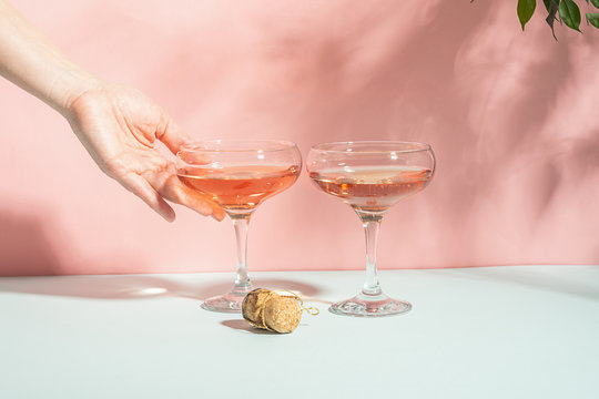 Female hand elegantly holding a glass of champagne or wine delicate pink background bright sunlight. Concept minimalism.