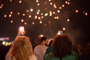 View from the back at people shooting fireworks on the phone defocused image, festive concept.