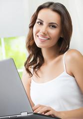 Cheerful beautiful girl using laptop, indoors