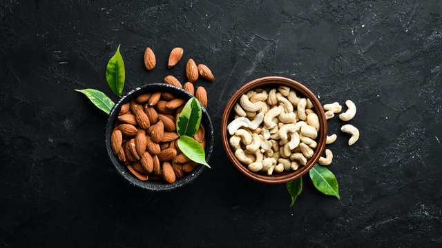 Nuts Cashew and Almond in a bowl on a black background. Top view. Free space for your text.