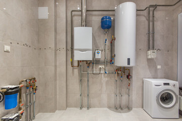 Wall hung gas boiler and electric water heater in boiler room