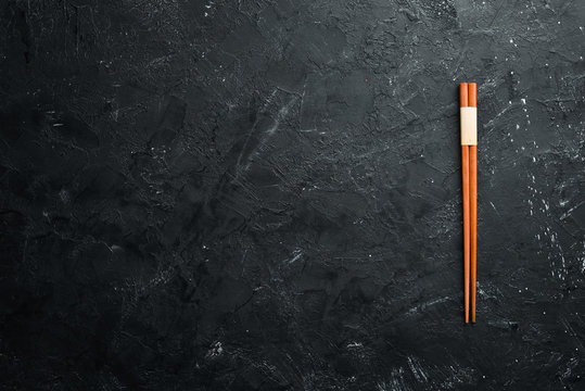 Wooden chopsticks on a black stone background. Top view. Free space for your text.