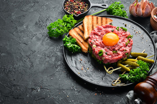 Beef steak tartare with raw egg yolk, pickled cucumber and onions. French cuisine. Top view. Free space for your text.