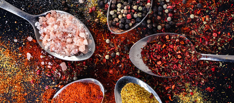 Spoons with different indian spices scattered on background table, peppercorn paprika salt turmeric powder, red, yellow and pink herbs seasoning top view, horizontal banner header for website design