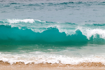 Fototapete - Blue and aquamarine color sea waves and yellow sand  with white foam. Marine beach background.