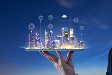 Waiter hand holding an digital tablet with Smart city with smart services and icons, internet of things, networks and augmented reality concept , night scene .
