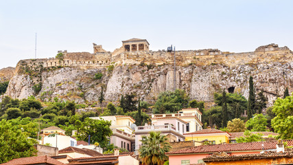 Fototapete - Acropolis of Athens behind Plaka district, Greece. It is a top landmark of old Athens. Panorama of the Acropolis hill with Ancient Greek ruins in the Athens center. Remains of the antique Athens city.