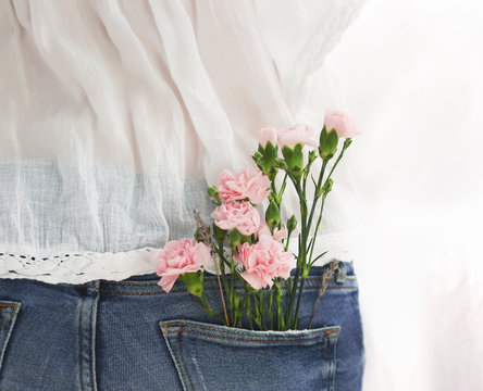 beautiful bouquet of a small carnation in a jeans pocket of a young girl