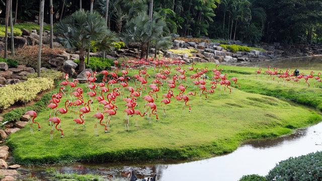 Flock of pink flamingos. Garden scultures in the Nong Nooch garden. Decorative statues of large exotic birds. Pattaya Thailand.