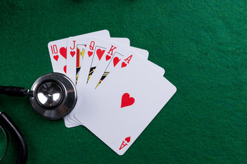 Stethoscope and poker playing cards as a gambling with your health concept. Royal flush of hearts