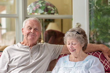 A senior man looks at the camera while his wife looks down. A beautiful senior couple in their seventies spends time together talking on their porch on a sunny day.