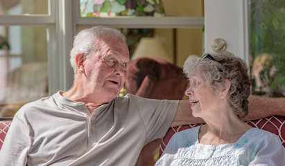 A senior woman talks to her husband. A senior couple in their seventies has a serious conversation together.