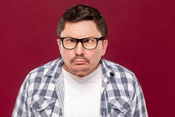 Closeup portrait of crazy funny middle aged business man in casual checkered shirt, eyeglasses and mustache standing with crossed eyes and looking. indoor studio shot, isolated on dark red background.