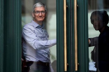 Apple Chief Executive Officer Tim Cook watches customers awaiting the grand opening of the new Apple Carnegie Library store in Washington