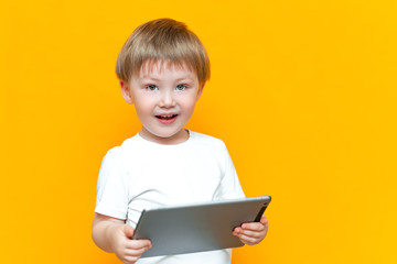 Surprised blonde three years old boy with his mouth open surprised, holding in his hands a tablet pc and looking at the camera on yellow background