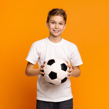 Boy posing with soccer ball on orange studio background