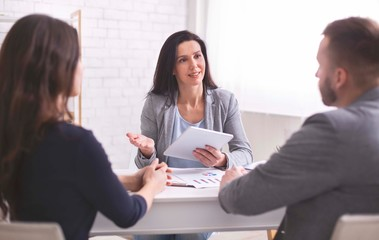 Professional woman talking to young couple at personal meeting
