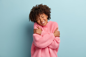 Obraz Love yourself concept. Photo of lovely smiling woman embraces herself, has high self esteem, closes eyes from enjoyment, likes her new comfortable soft pink sweater, tilts head, stands indoor - fototapety do salonu