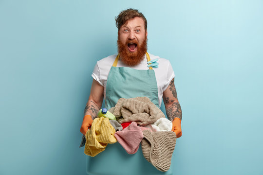 Horizontal shot of desperate redhead man shouts with annoyance, holds basin with pile of dirty laundry, has tattoos on arms, wears casual t shirt and apron, isolated over blue wall. Domestic chores