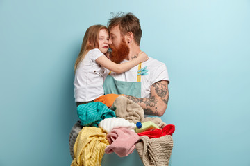 Image of single father holds crying small daughter, doind laundry at home, stand near basket with laundry and bottle of liquid powder, isolated on blue background. Household and children upbringing