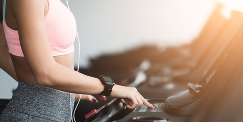 Adjusting speed. Woman training on treadmill in gym