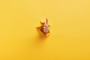 Image of unrecognizable man makes thumb up gesture, demonstrates approval or agreement, gestures through torn paper wall yellow background. Body language concept. Hand sign. Hole in wall. Like gesture