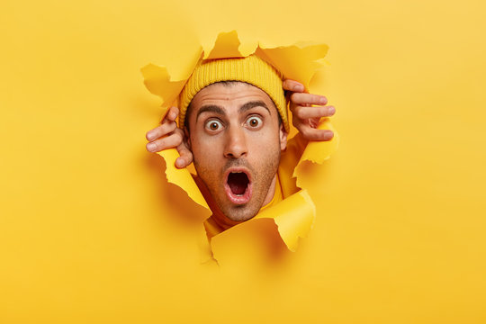 Headshot of stupefied young man with European appearance, wears yellow hat, keeps head in torn paper wall, keeps jaw dropped from surprisement, impressed by sudden bad news or rumor. Omg concept