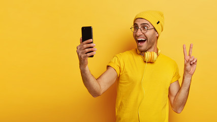 Studio shot of cheerful Caucasian young man makes peace sign, holds cell phone, takes selfie portrait, makes video call, wears yellow clothes, models indoor, empty space for your advertisement.
