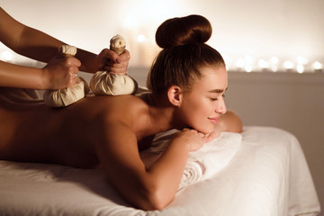 Thai Herb Compress Massage. Woman Relaxing In Spa