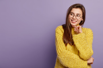 Smiling Caucasian female model touches gently chin, looks with toothy smile aside, admires something beautiful, wears big optical eyewear and sweater, stands over purple background with blank space Wall mural