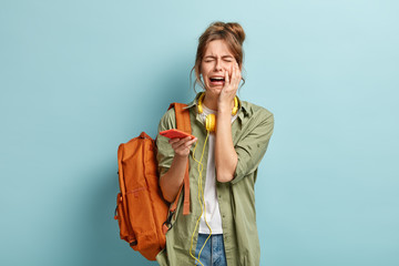 Depressed dejected female cries holds mobile phone, has problem with internet connection, checks email, has bag on shoulder, dressed casually, isolated over blue background. Negative emotions