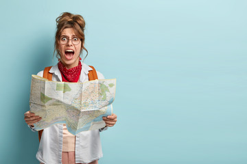 Photo of frustrated woman traveler lost in city, looks depressed at paper map, shouts from despair, has tour on vacation, carries backpack, wears big round spectacles models indoor copy space for text