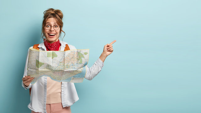 Smiling optimistic young European female guide holds map, shows direction to tourist away, demonstrates destinations of showplace, dressed casually, isolated on blue wall, searches right route