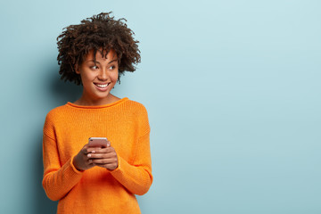 Photo of cheerful delighted African American woman types sms on modern cell phone device, enjoys...