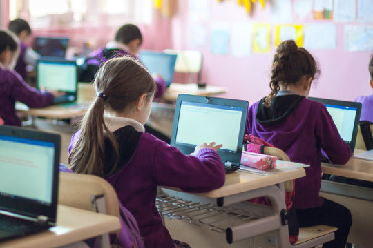 school children are participating actively in class, working at laptop