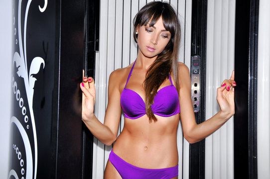 Young beautiful sexy brunette woman in violet bikini standing and tanning in solarium ultraviolet lamps with blue light.