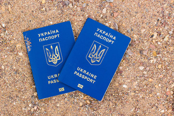 Ukrainian passports documents covers lay on sand ground background picture, copy space