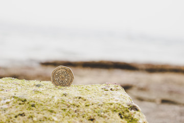 Jordanian single coin stay on the edge on stone, wallpaper pattern picture with empty copy space for text