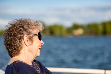 Beautiful,confident senior woman smiles and poses while boating on a beautiful lake on a sunny day.
