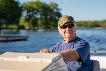 A senior man enjoys driving a boat on a beautiful lake on a sunny day.